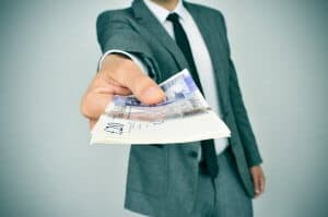 a young man in suit giving a wad of pound sterling bills to the observer