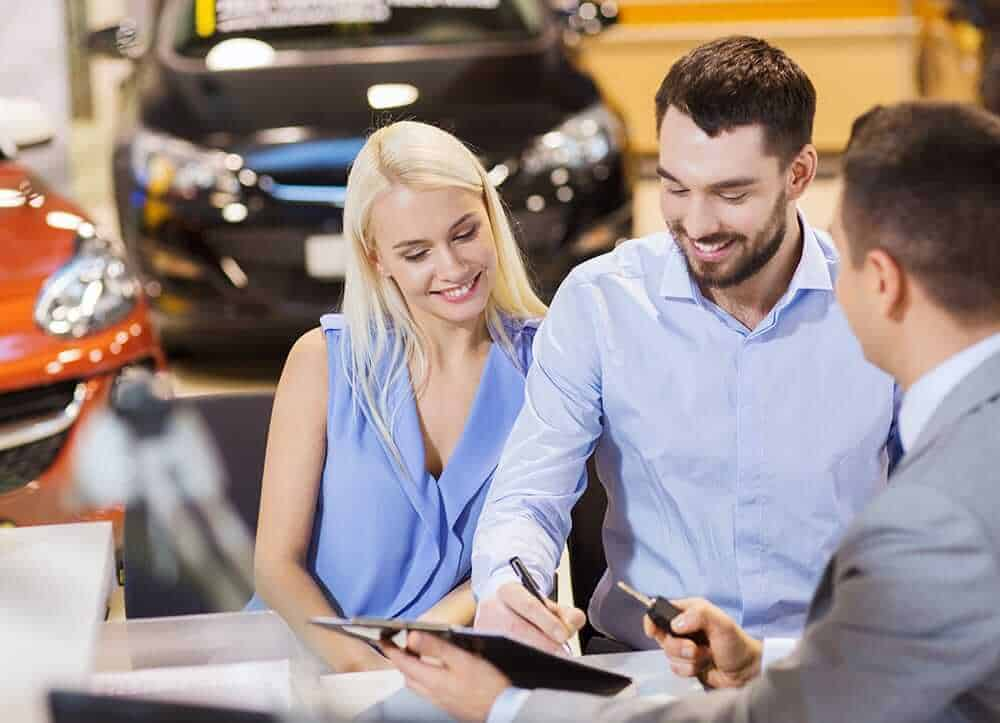 couple is buying a car at dealership