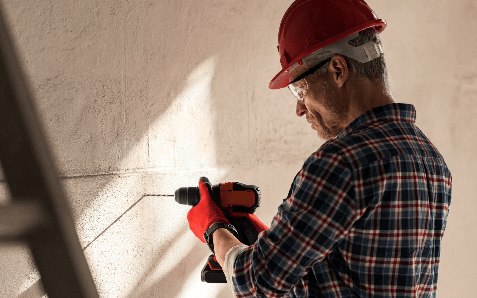 Man drilling brick wall