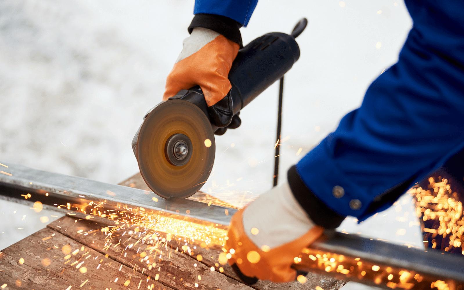 Man grinding metal in overalls