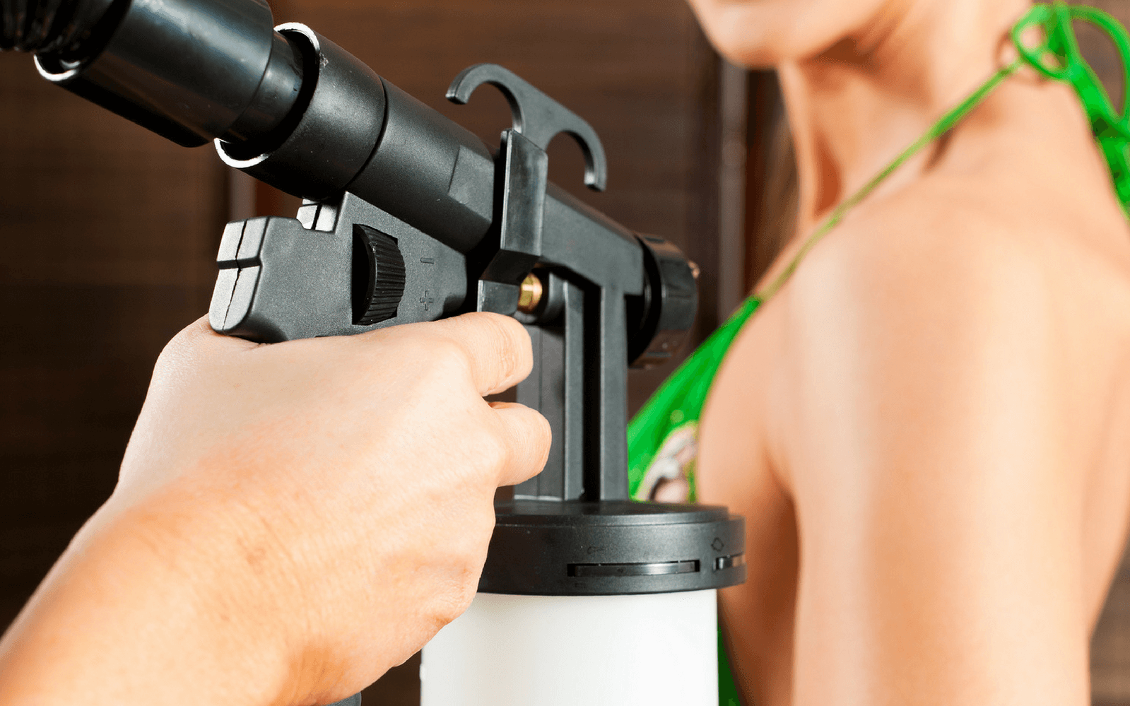 Woman being spray tanned close up