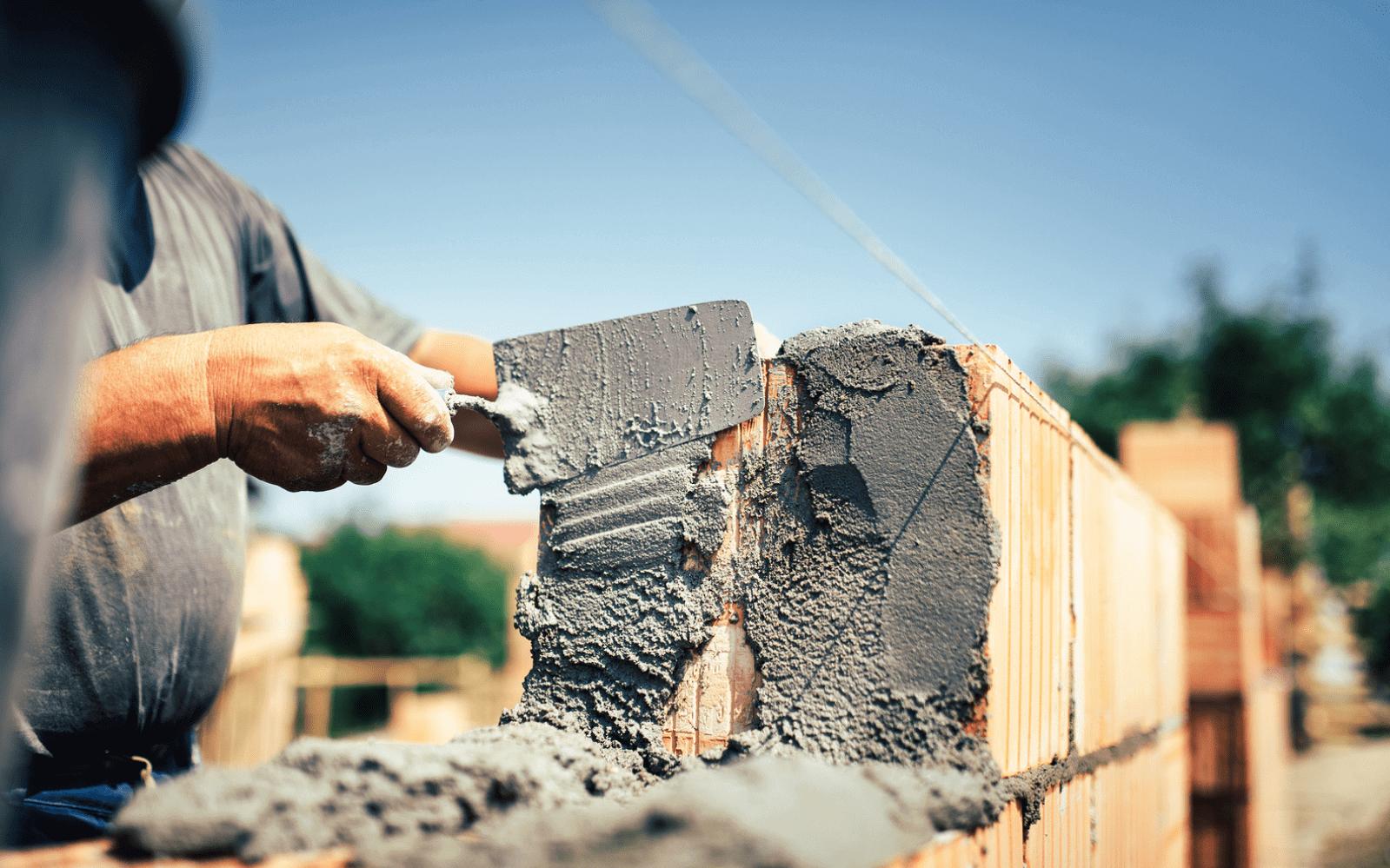 Industrial worker creating brick wall