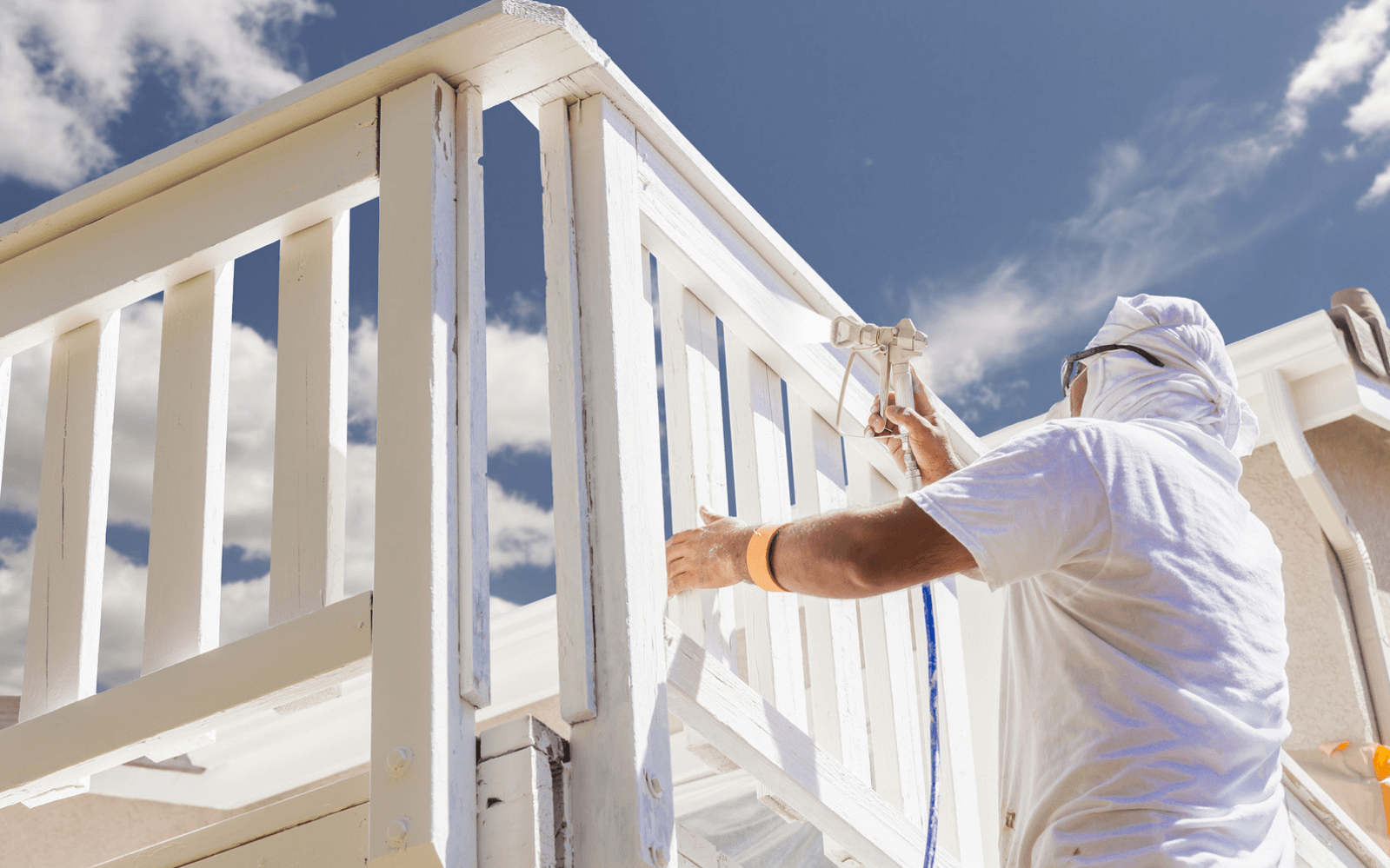 House painter spray painting fence