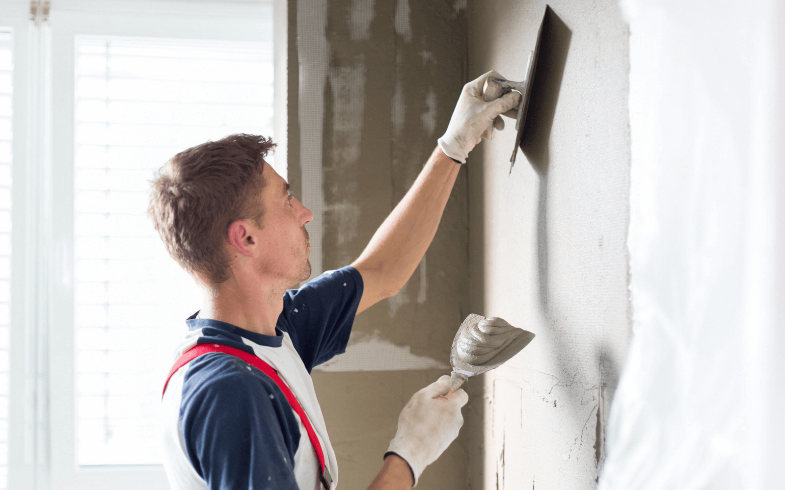Young man plastering wall