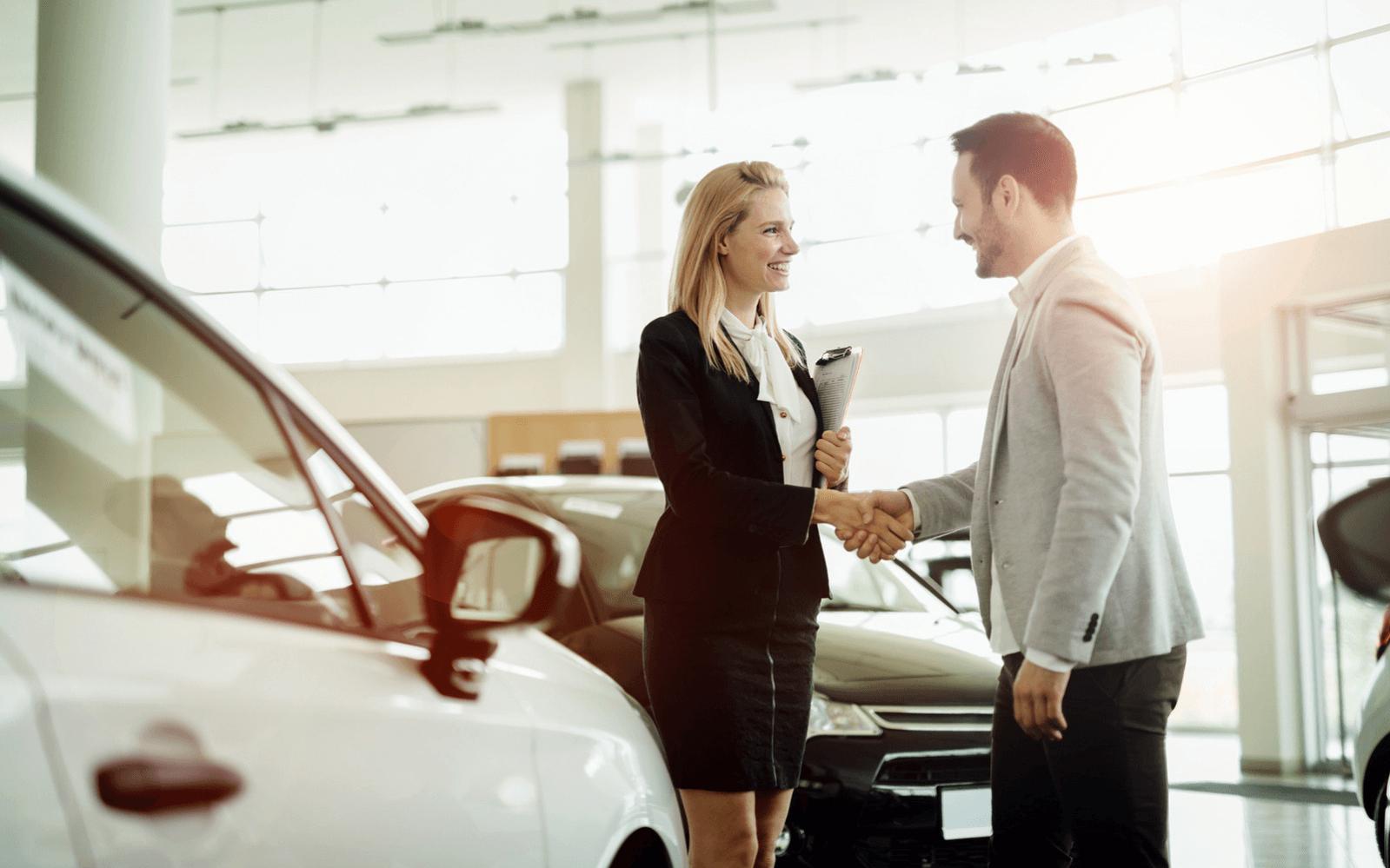 Car saleswoman shaking customer's hand