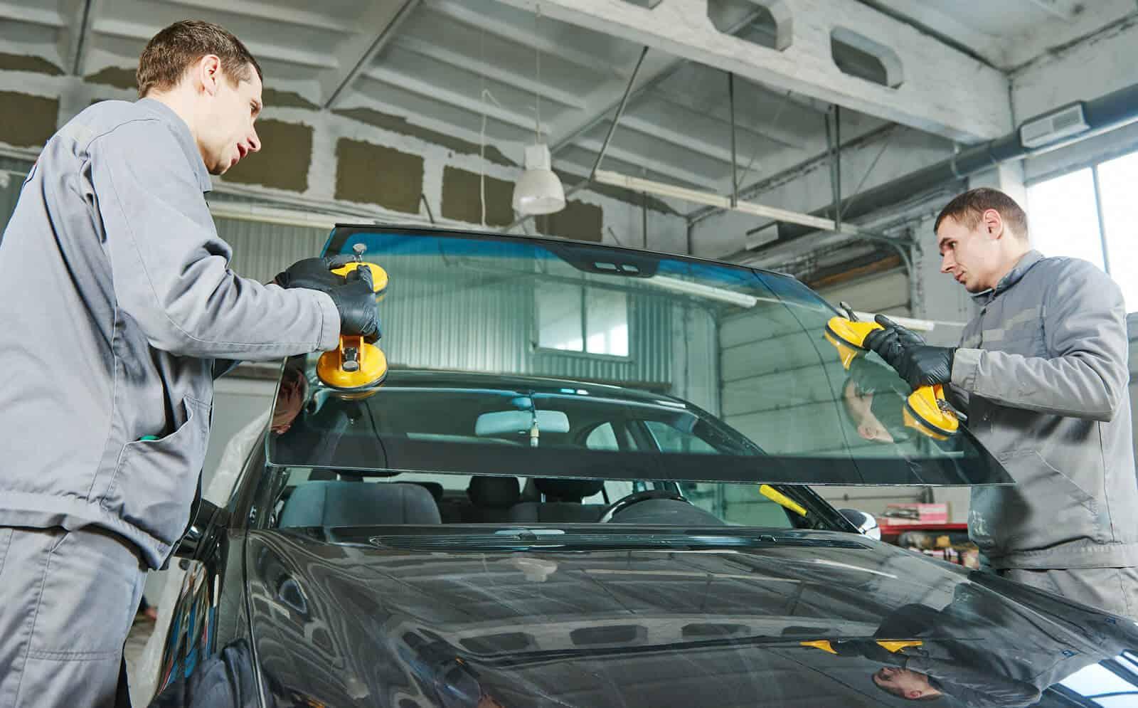 Mechanics replacing windscreen