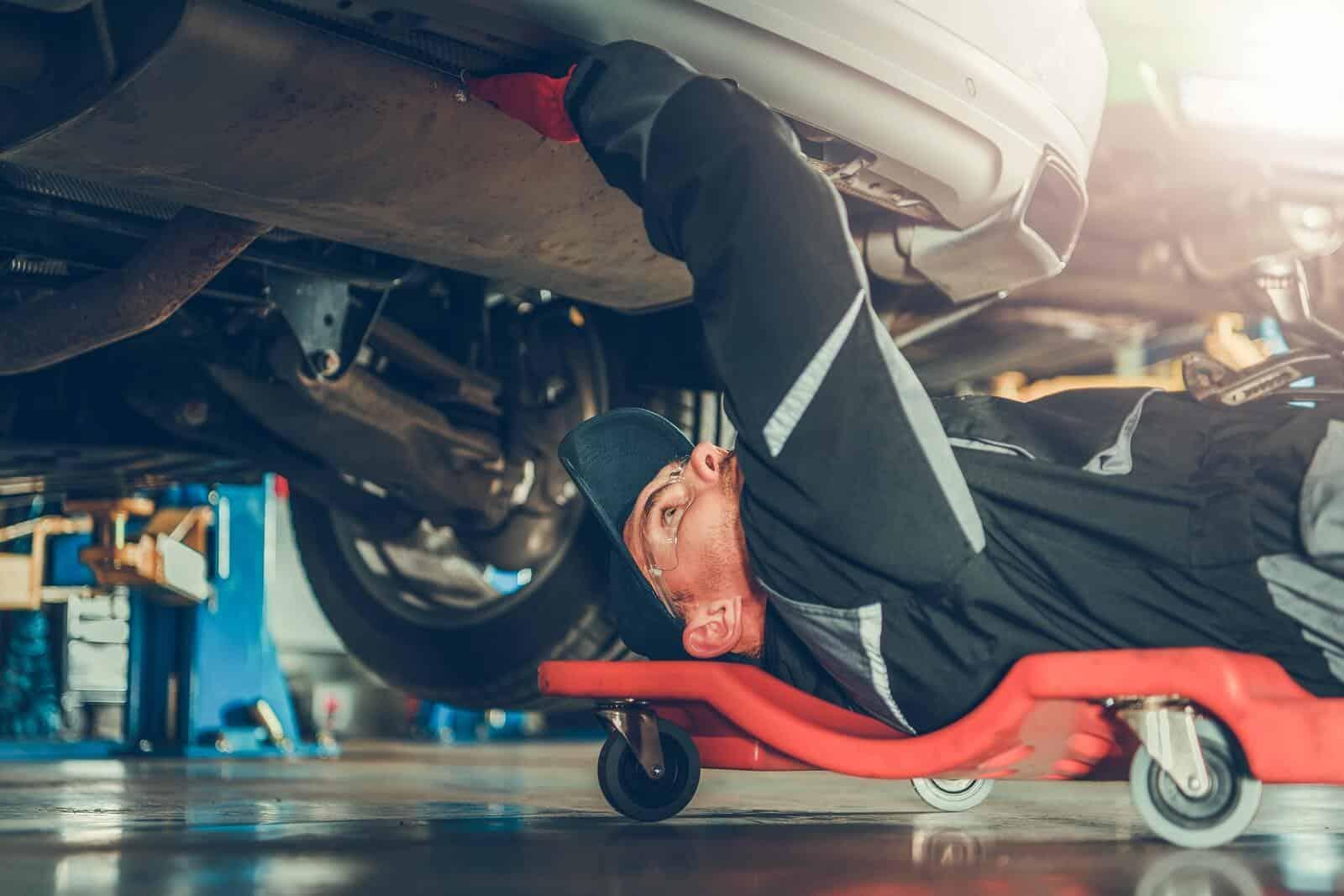Car mechanic beneath car