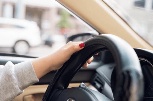 Woman's hands on steering wheel
